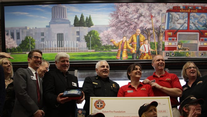 Salem Fire Chief Mike Niblock, center, accepts a check for $18,705 woth of automated external defibrillators, or AEDs on Thursday, Feb. 16, 2017 at the Firehouse Subs Restaurant on 3810 Commercial St. SE in Salem.