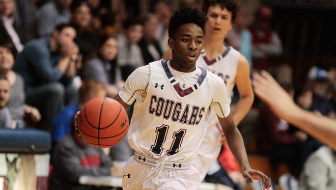 St. Thomas More's Jonathan Cisse drives the ball against E.D. White in first half action of the Cougars' 85-41 quarterfinals win in Lafayette Friday, March 3, 2017.