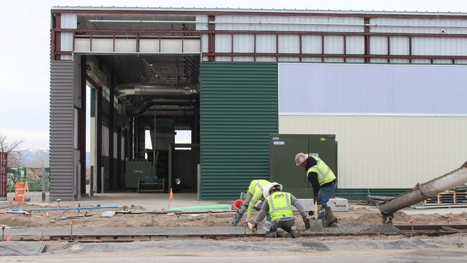 Workers put in a sidewalk March 10 at Waste Management's Eco-Center on Commercial Row. The facility is expected to be fully online this summer.