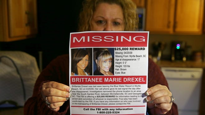Dawn Pleckan, the mother of Brittanee Drexel, holds a pamphlet for a foundation she created to help families going through a missing person case.