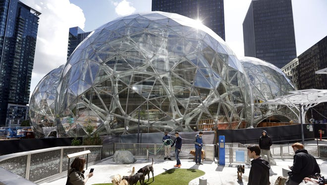 Amazon employees tend to their dogs in a canine play area adjacent to where construction continues on three large, glass-covered domes as part of an expansion of the Amazon.com campus, Thursday, April 27, 2017, in downtown Seattle.