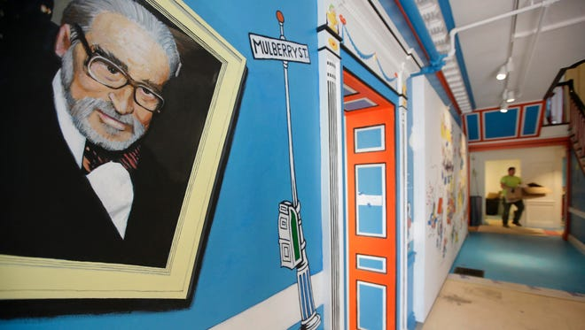 In this May 4, 2017, photo a mural that features Theodor Seuss Geisel, left, also know by his pen name Dr. Seuss, rests on a wall near an entrance at The Amazing World of Dr. Seuss Museum, in Springfield, Mass. The new museum devoted to Dr. Seuss opened on June 3 in his hometown. (AP Photo/Steven Senne)