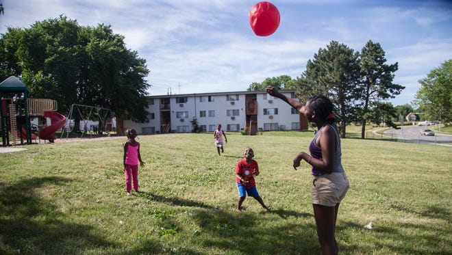 A group of children play outside of the River Hills Apartments on Tuesday, June 20, 2017, in the East Village.