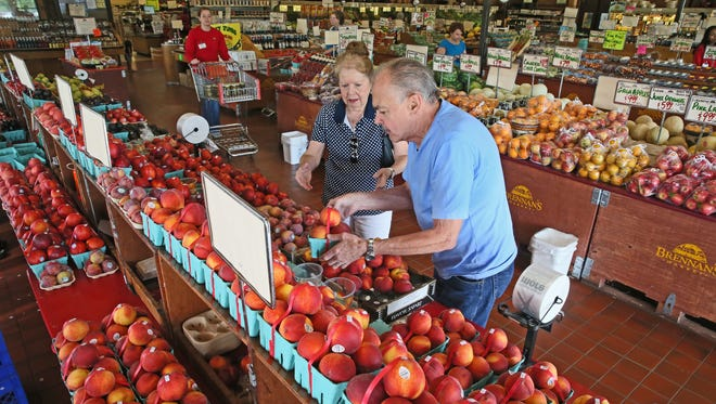 Paul and Karen Suchocki of Brookfield select some peaches at Brennan's Market in Brookfield.