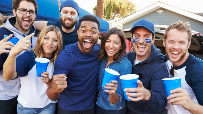 Group Of Sports Fans Tailgating In Stadium Car Park