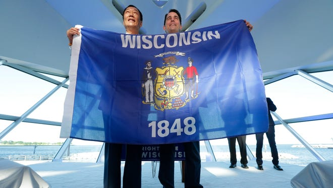 Gov. Scott Walker (right) and Foxconn Technology Group Chairman Terry Gou hold a Wisconsin flag at the Milwaukee Art Museum on July 27 to celebrate Foxconn's $10 billion investment to build a display panel plant in Wisconsin that could employ up to 13,000 workers and draw up to $3 billion in subsidies from state taxpayers.