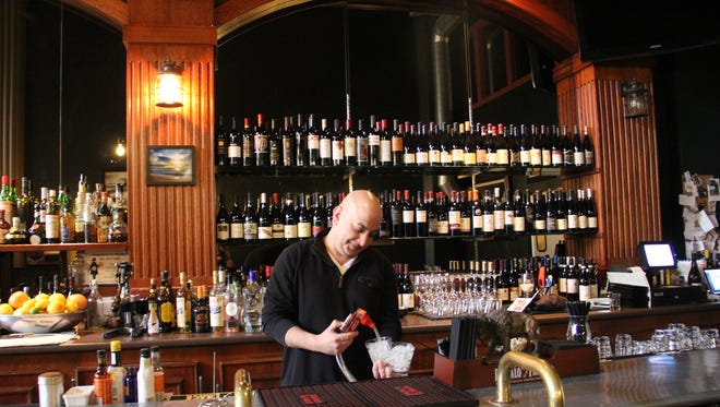 Owner Bruce Rafaei pours water at the bar of his restaurant, Bari