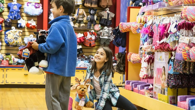 Alaina Powgnas, 9, and her brother Landis, 8, shop at Build-A-Bear Workshop on Black Friday at Arrowhead Towne Center in Glendale on Nov. 24, 2017.