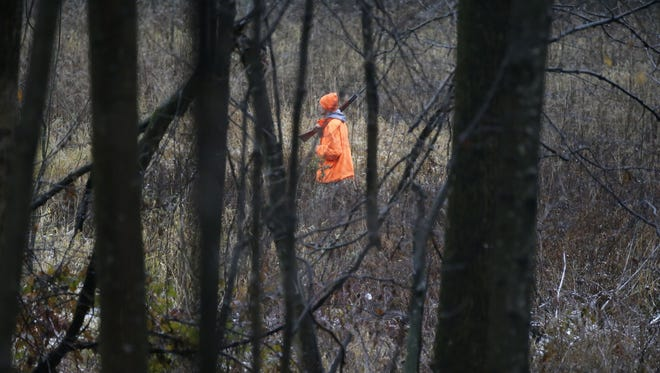 A hunter walks in a field on the opening day of the gun-deer season in the town of Herman in 2017.