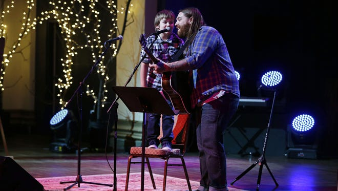 Christopher Gold sings with his son, Oliver, as they perform during the seventh annual toy drive to benefit Harbor House Domestic Abuse Services Dec. 9 at the OuterEdge in Appleton.
