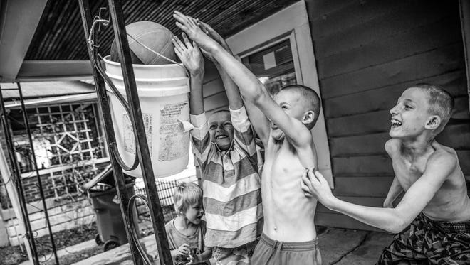 Brothers Theo Patrick Johnson III, 11, Chad Johnson, 8, and Jacob Ryan Johnson, 7, play porch basketball at their home on Indianapolis' near-westside on Thursday, July 6, 2017.
