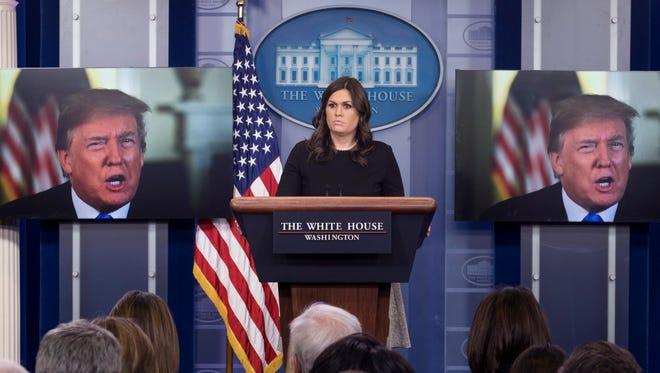 White House Press Secretary Sarah Huckabee Sanders stands beside monitors showing President Trump delivering a statement on the economy, at the beginning of a news conference in the James Brady Press Briefing Room of the White House in Washington, D.C., Jan. 4 2018.