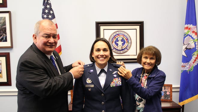 Congressman Gregorio Kilili Camacho Sablan, left, and Rita Sablan Dutton (mother), right, pin the silver eagle insignia to Esther Camacho Sablan during her promotion ceremony in Jan. 11, 2018 at the Marianas congressional office in Washington, D.C. Esther was believed to be the first woman in the Northern Marianas to be promoted to Colonel in any of the U.S. Armed Services.