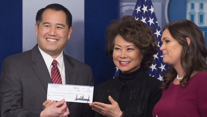 The Department of Transportation's Under Secretary for Policy Derek Kan and Transportation Secretary Elaine Chao accept the the salary check of President Trump.