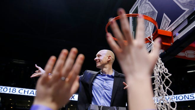 Xavier Musketeers head coach Chris Mack throws out pieces of the net after the NCAA Big East game between the Xavier Musketeers and the Providence Friars at the Cintas Center in Cincinnati on Wednesday, Feb. 28, 2018. The Musketeer won its first-ever Big East regular season title with an 84-74 win over Providence.