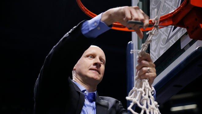 Xavier Musketeers head coach Chris Mack cuts down the net after the NCAA Big East game between the Xavier Musketeers and the Providence Friars at the Cintas Center in Cincinnati on Wednesday, Feb. 28, 2018. The Musketeer won its first-ever Big East regular season title with an 84-74 win over Providence.