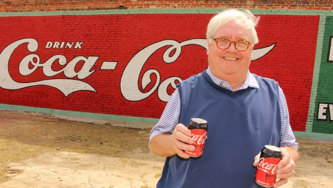 Selma banker Catesby Jones enjoys a Coca-Cola near a new wall painting of the popular soft drink.