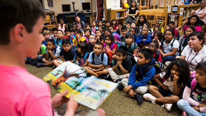 """Child author Tommy Belle, 10, reads his book titled """"Freeda the Cheeta"""" to kindergarten and first-grade students at Eden Park Elementary in Immokalee on Wednesday, April 4, 2018. Each of the students, who are a part of The Immokalee Foundation's Immokalee Readers program, received a copy of the books after the reading."""