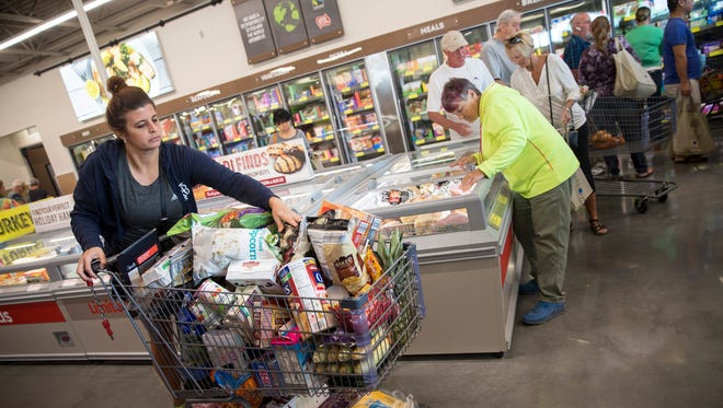 Susan Burlinson, of Naples, fills her cart during the grand opening of the first Aldi grocery store in Naples on Thursday, Nov. 17, 2016. The first 100 shoppers received a golden ticket, each containing Aldi gift cards ranging from $10 to $100.