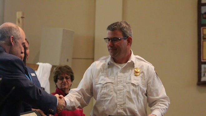 Marion Township Fire Chief Ben Meddles accepts a certification of appreciation on his department's behalf.
