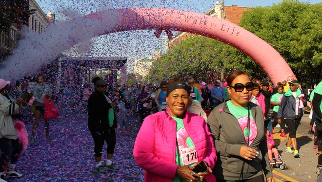 Two Joy to Life walkers emerge into the sunshine during Saturday's event that drew a big crowd in Montgomery on Saturday.