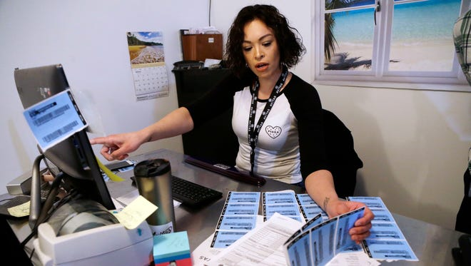 In this March 30, 2018, photo, Cecilia Espinoza checks printed product bar codes against their computer database at Avitas marijuana production facility in Salem.