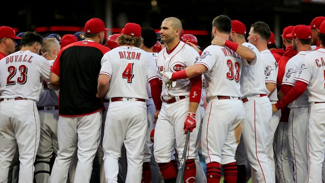 Cincinnati Reds first baseman Joey Votto (19), center, is restrained after exchanging words with Milwaukee Brewers catcher Erik Kratz (15) in the third inning during a National League baseball between the Milwaukee Brewers and the Cincinnati Reds, Thursday, June 28, 2018, at Great American Ball Park in Cincinnati.