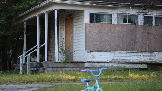 Two young girls played outside on Cherry Street, their home in between two boarded-up houses, including this one.