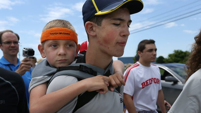 Braden Gandee rides on his brother Hunter's shoulders as they close in on the final miles of their 40-mile walk from Bedford to Ann Arbor on June 7, 2014.