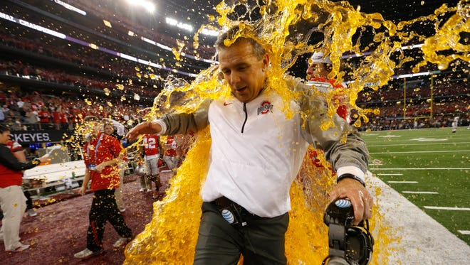 Ohio State coach Urban Meyer is drenched as the Buckeyes celebrate their victory 42-20 over Oregon in the national championship on Monday.
