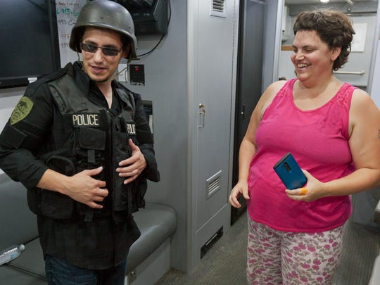 Dan Banas, of Seattle, tries on some of the Ithaca Police Department's equipment as he and his sister Susan Brown of Ithaca, and a resident of West Village, tour the IPD's SWAT vehicle during community gathering held in August by the management company of the West Village apartment complex.   SIMON WHEELER/Staff Photo