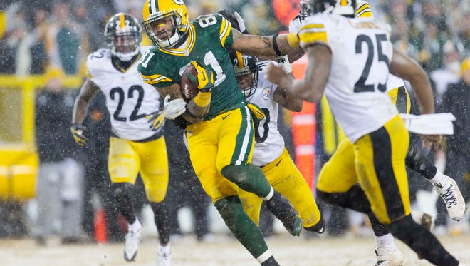 Green Bay Packers tight end Andrew Quarless (81) rushes with the football after catching a pass as Pittsburgh Steelers safety Will Allen (20) defends  during the fourth quarter at Lambeau Field.
