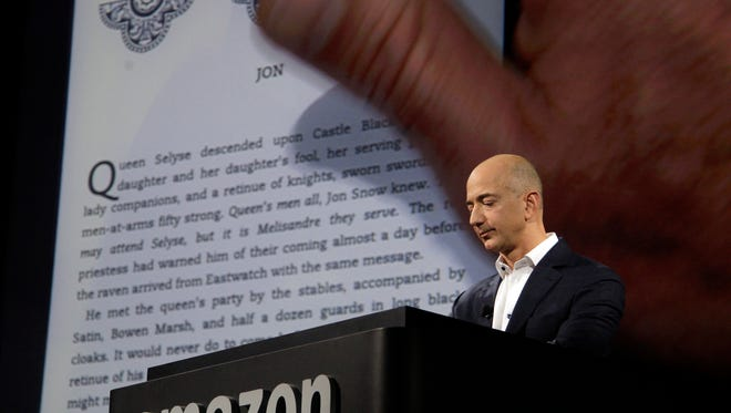 Jeff Bezos, CEO and founder of Amazon, demonstrates a Kindle paperwhite tablet in 2012.