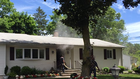 Smoke comes through the roof and front of a North Pascack Road house during a fire Monday