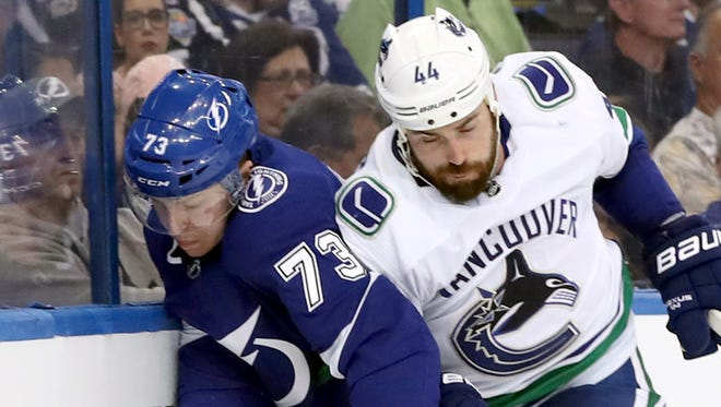 Canucks defenseman Erik Gudbranson, right, defending against Lightning left wing Adam Erne, would have been sought by some teams if he had not signed an extension.