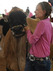 Taylor Lutz leads a dairy cow into the show ring during
