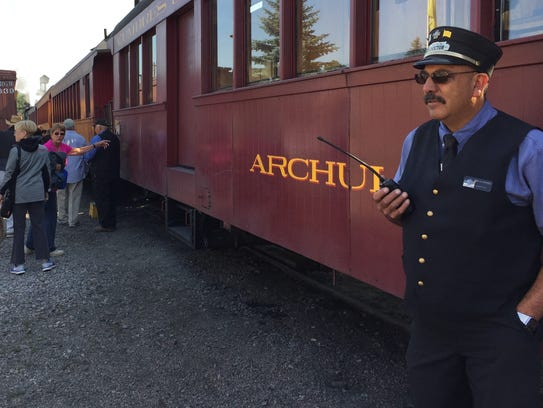 A conductor watches as passengers get ready to climb