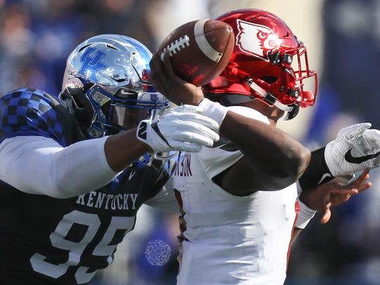 Lamar Jackson is hit by Kentucky's Quinton Bohanna in the first half.November 25, 2017