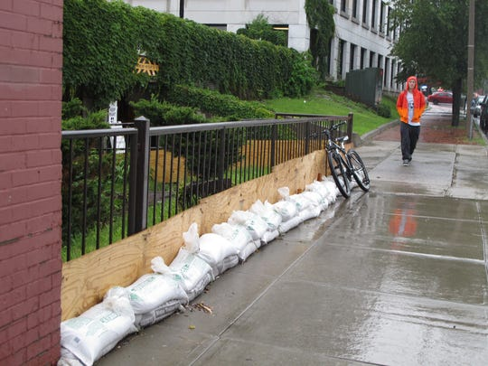 A sandbag-and-plywood barricade protects an old Ravine trace (the western edge of South Winooski Avenue and King Street) from flooding. The makeshift barrier has been replaced with a low concrete wall.
