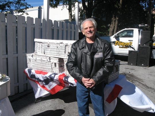 John J. Falcone, 76, father of late City of Pough keepsie Det ective John M. Falcone, stands Sunday with release bas kets of white pigeons at the annual memorial motorcycle ride for his son.