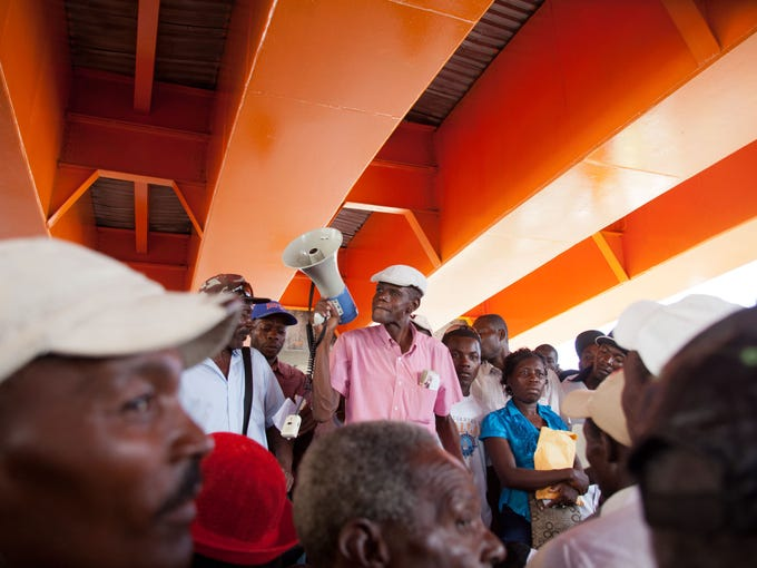 Current and retired Haitian sugarcane workers listen