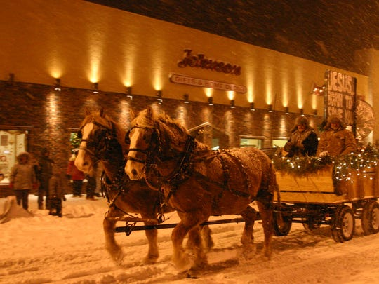 A horse-drawn wagon rides by Johnson's Pharmacy in