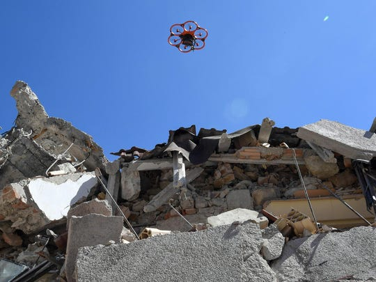 A drone flies over the debris of a school in Amatrice