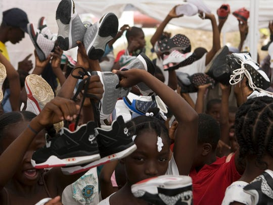 Haitian students hold up confiscated shoes that were