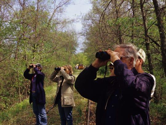 Bird watchers look for birds in the Tiffany Wildlife