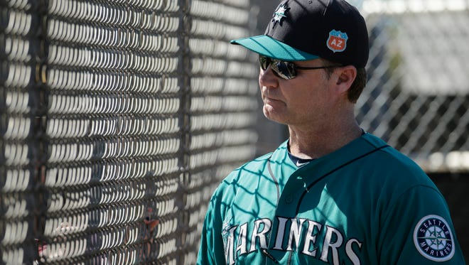 Seattle Mariners manager Scott Servais talks to a fan through a fence during spring training baseball practice Monday, Feb. 22, 2016, in Peoria, Ariz. (AP Photo/Charlie Riedel)