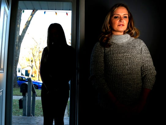 Ashley, of Brighton, stands in her family room on Wednesday,