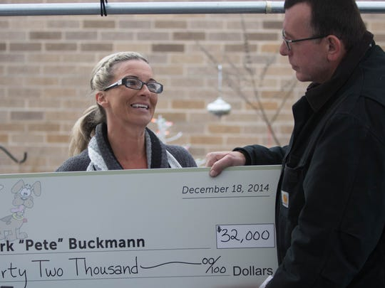 Pete Buchmann in 2014 receives a giant check for $32,000 from Donna Vanderhuevel. Vanderhuevel started a GoFundMe campaign for Buchmann after hearing that Buchmann walked five miles a day to be with his dog, Buster, at Faithful Friends while he was homeless.