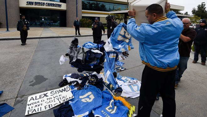 A former Chargers fan dumps memorabilia in front of the San Diego Chargers headquarters after the team announced it will move to Los Angeles Thursday.