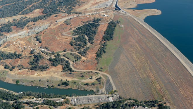 "The Lake Oroville Dam and damaged controlled spillway are seen in May during a flight over the area with Oroville pilot Gonzalo ""Pee Wee"" Curiel. The authors of a new report are concerned about a green spot on the dam's face that may be vegetation growing with the aid of a water leak."